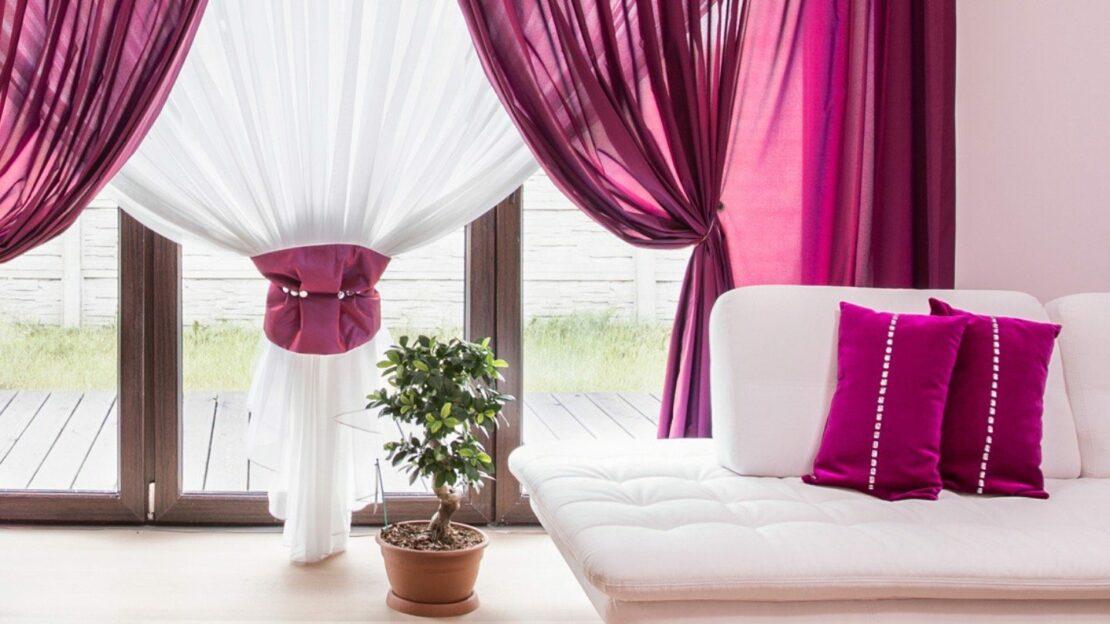 Farbige Akzente in den Gardinen gestalten das Wohnzimmerfenster