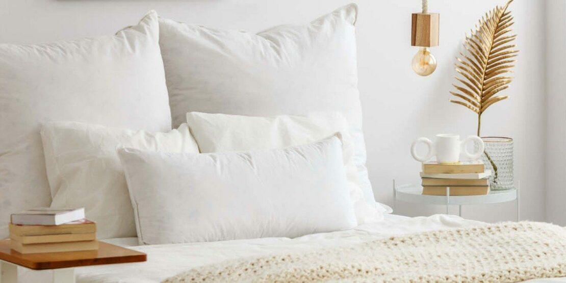 Weiße Kissen, goldene Accessoires im Schlafzimmer