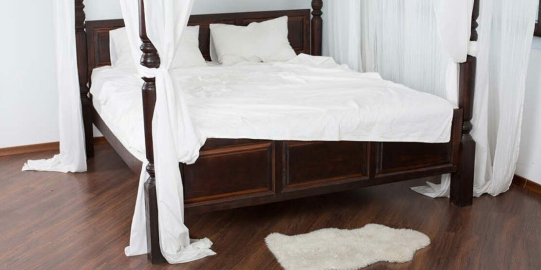 Bett im Kolonialstil mit dunklem Holz