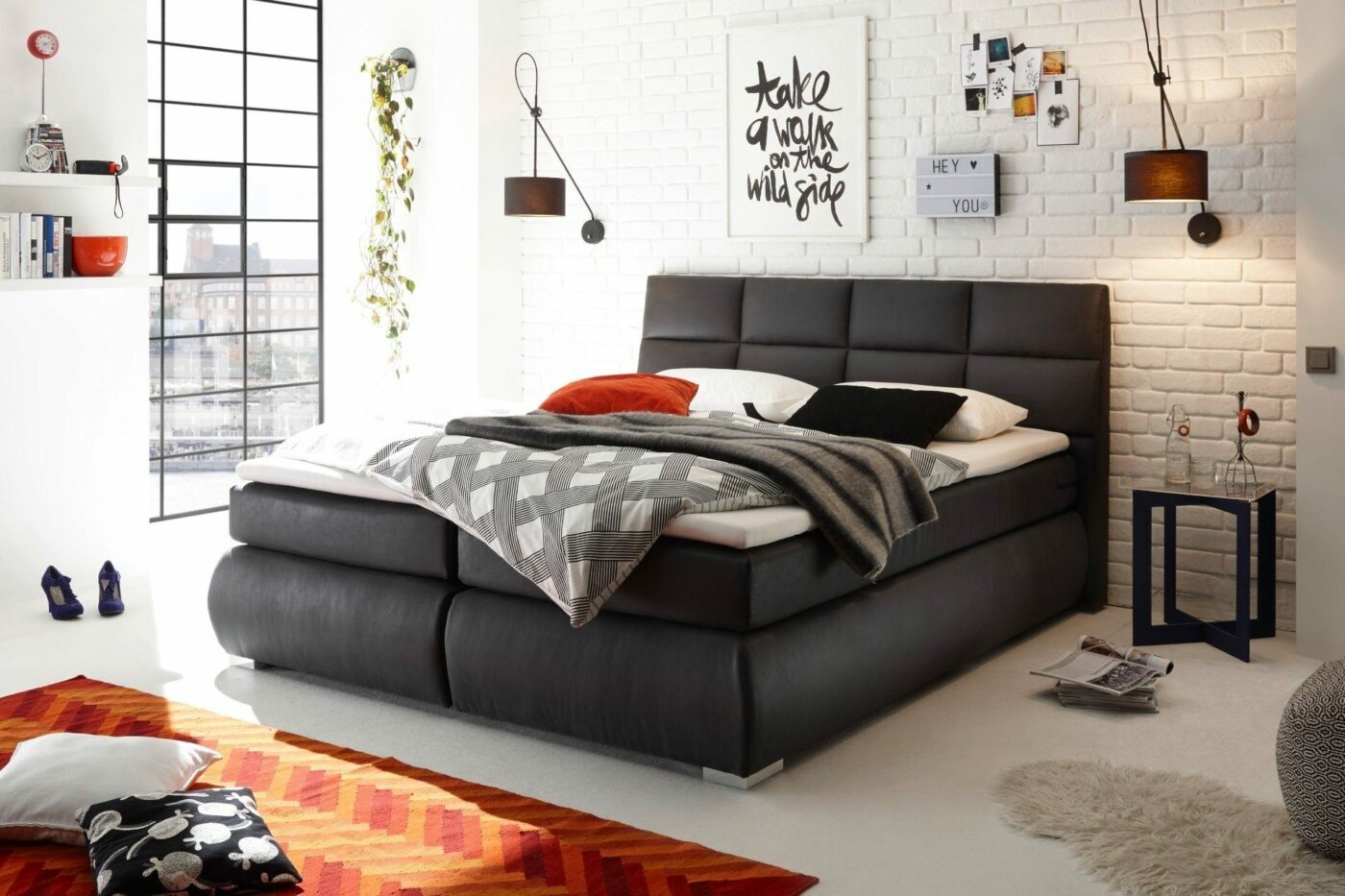 Dunkelgraues Bett vor weißer Ziegelwand