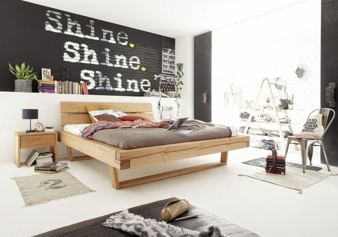 Bett mit Holzrahmen im Timber-Look vor Wand mit Schriftzügen