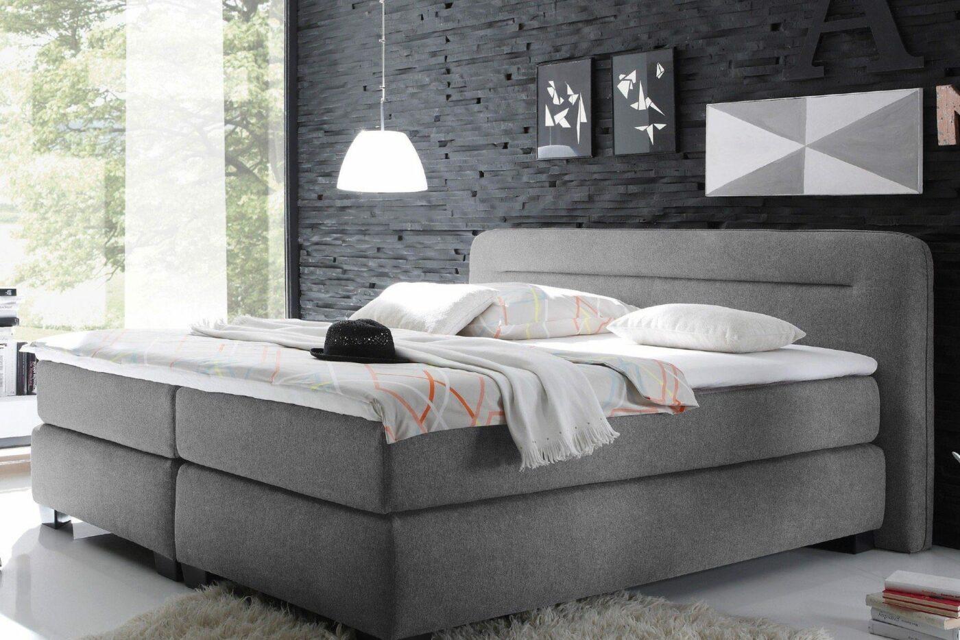 Graues Bett mit Stoffbezug vor dunkler Wand im Schiefer-Look