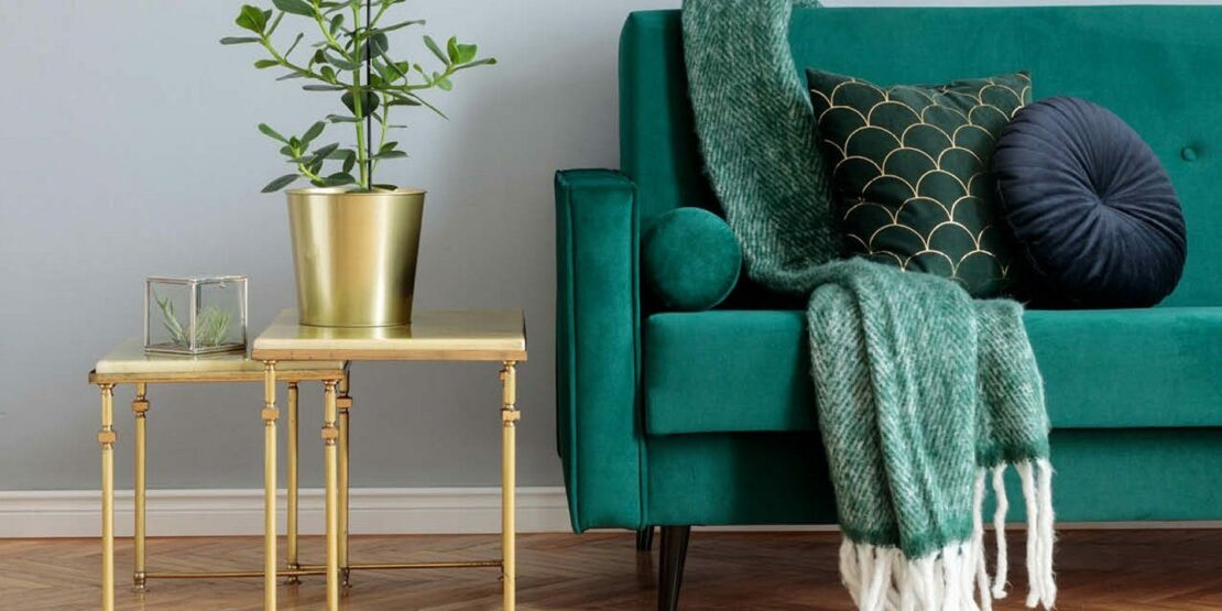 Dunkelgrüne Couch mit goldenem Beistelltisch