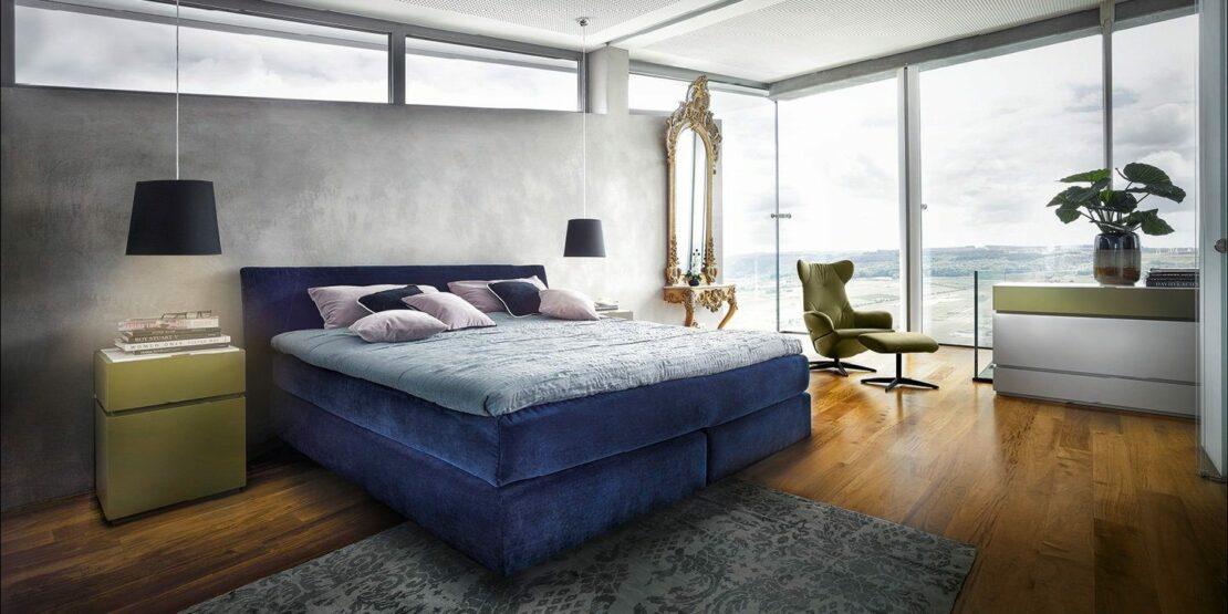 Blaues Boxspringbett in modern eingerichtetem Schlafzimmer