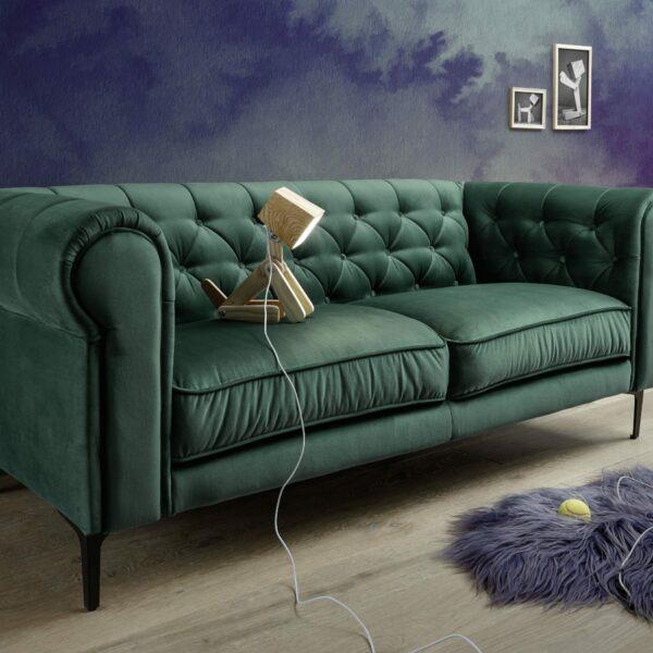 """Sofa """"Gacel"""" mit Bezug 312/52 in Tannengrün und Füßen aus schwarzem Metall - Wohnbeispiel."""