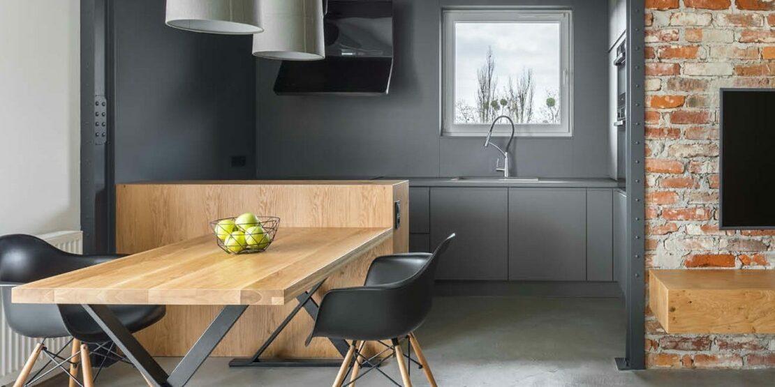 Graue Küche mit Holz und sichtbaren Ziegeln