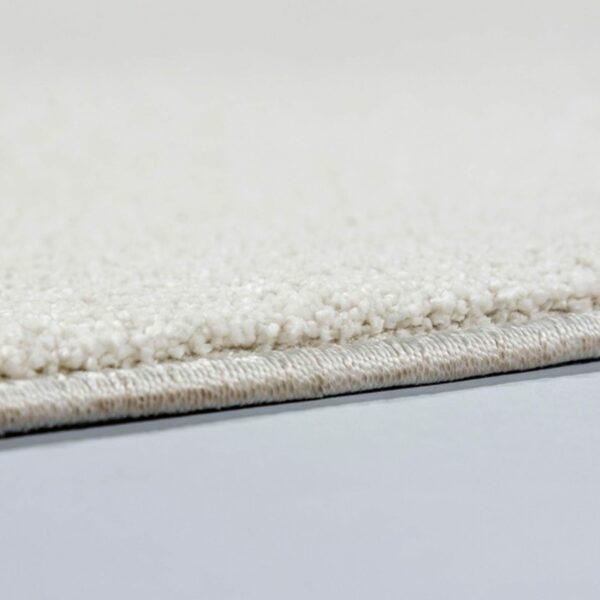 """Astra """"Pure"""" Teppich in der Farbe Creme zeigt Nahansicht der Kante."""