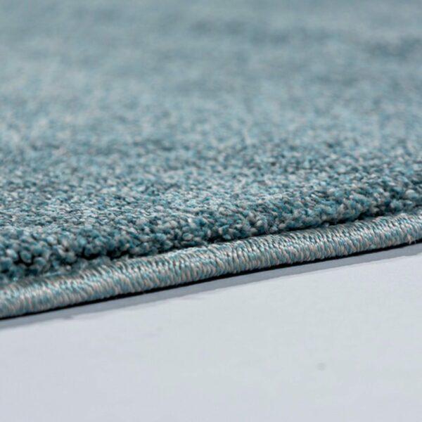 """Astra """"Pure"""" Teppich in der Farbe Türkis zeigt Nahansicht der Kante."""