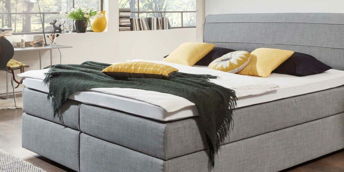 Minimalistisches, graues Boxspringbett in einem Schlafzimmer