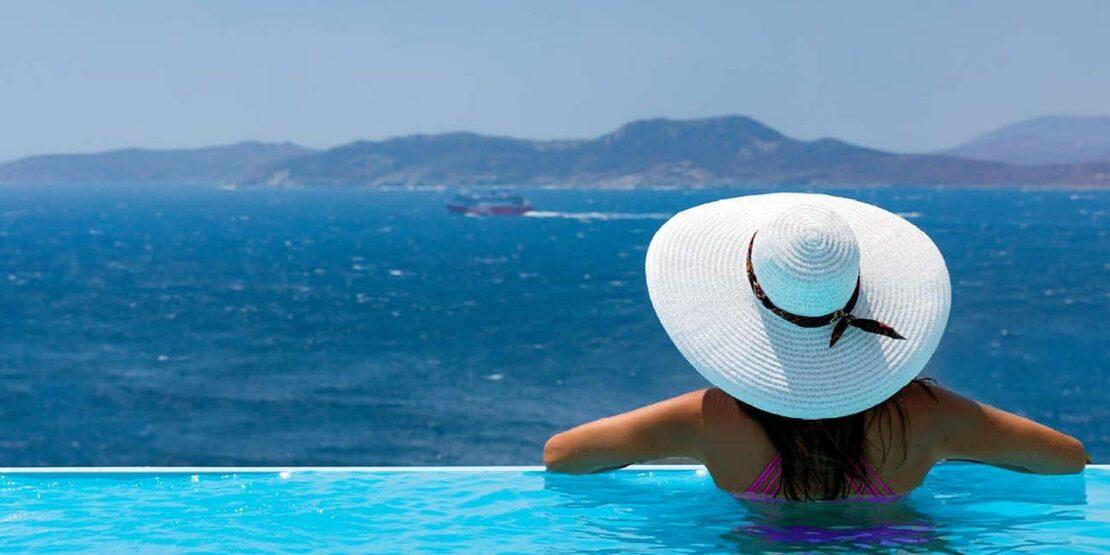 Frau schaut aus einem Infinity Pool aufs Meer hinaus