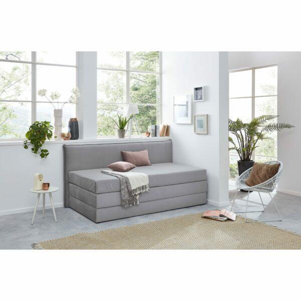 """Trendstore """"Helda"""" Boxspring-Umbauliege mit Rückwand, in der Farbe Grau, im Milieu."""