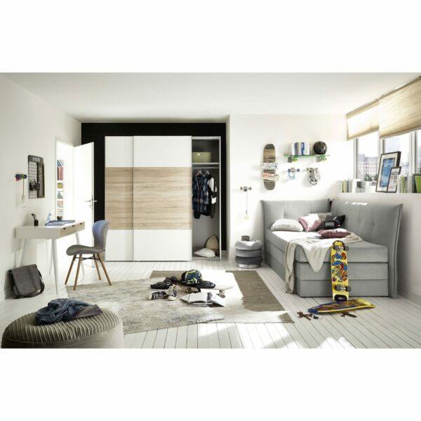 """Trendstore """"Helda"""" Boxspring-Umbauliege mit Rückwand und Seitenteil links, in der Farbe Grau, im Milieu."""