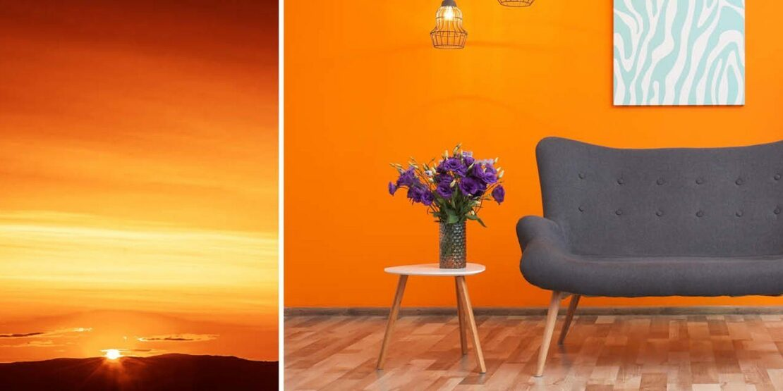 Sonnenuntergang und graue Couch vor Wand in Orange