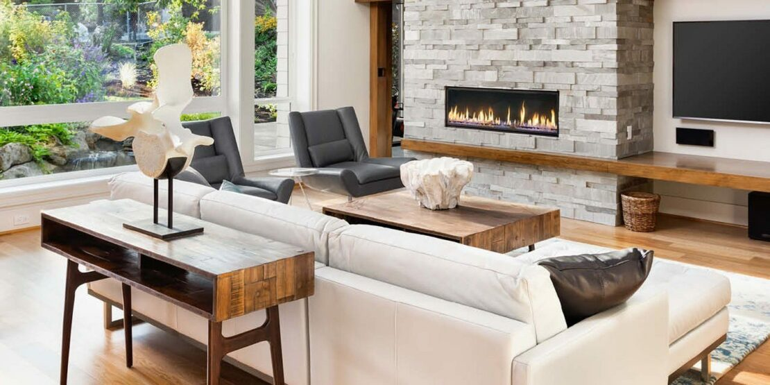 Lichtdurchflutetes Wohnzimmer mit Holzmöbeln und Kamin