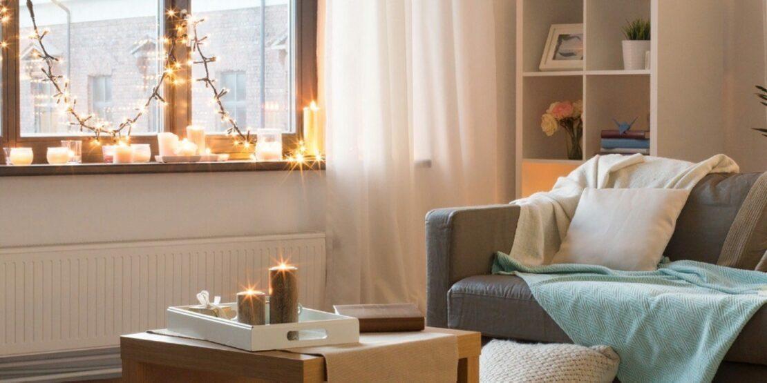 Gemütliches Wohnzimmer, dekoriert mit Lichterketten und Kerzen im Fenster und auf einem Beistelltisch
