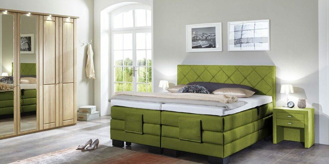 Schlafzimmer mit Spiegelschrank und grünem Boxspringbett
