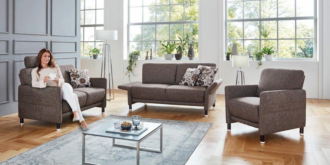 Zwei kompakte Sofas und Sessel in einem lichtdurchfluteten Wohnzimmer