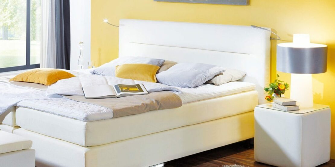 Weißes Boxspringbett in einem gelben Schlafzimmer