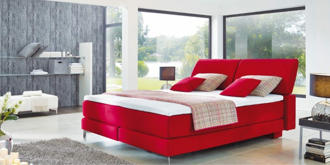 Schlafzimmer mit rotem Boxsprigbett und Regalen