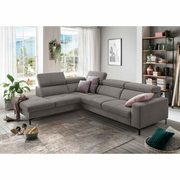 set one by Musterring SO 1300 Sofa mit Bezug in Mouse Grey und Ottomane links im Milieu.