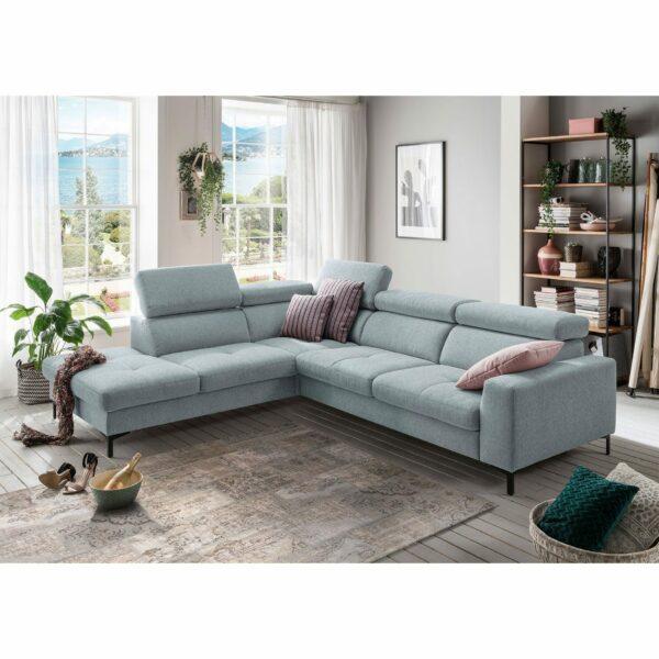 set one by Musterring SO 1300 Sofa mit Bezug in Pastel Blue und Ottomane links im Milieu.