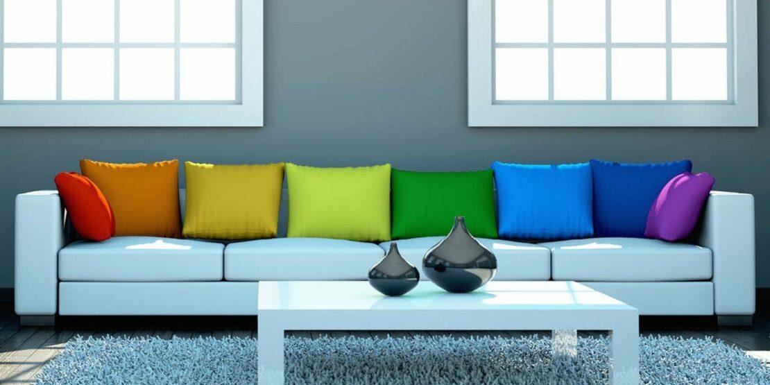 Weiße Couch vor grauer Wand mit acht Kissen in den Regenbogenfarben