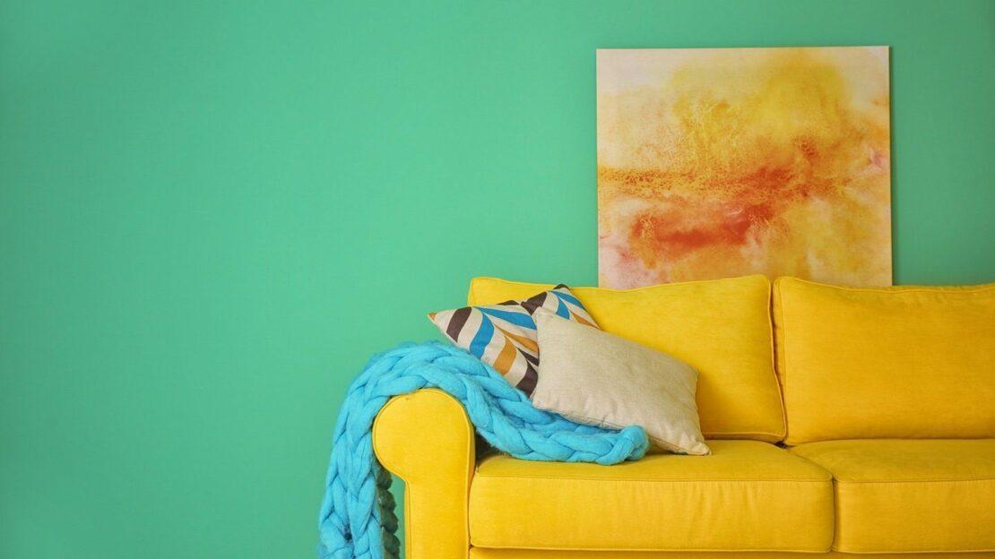 Beispiel für eine butne Einrichtung mit einem gelben Sofa, türkiser Decke, grüner Wand