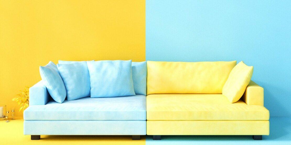 Eine hellblau-gelbe Couch vor einer gelb-hellblauen Wand